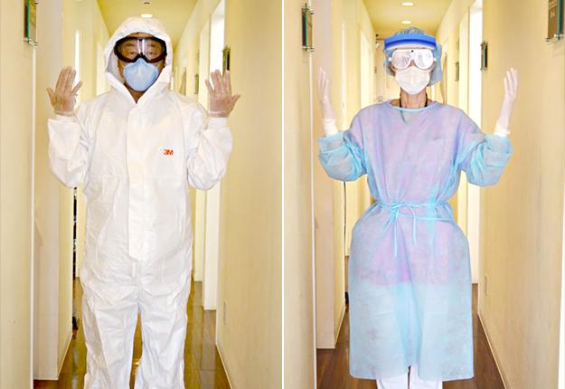 当医院スタッフがゴーグル、帽子、N95 マスク、感染予防着を着用している様子